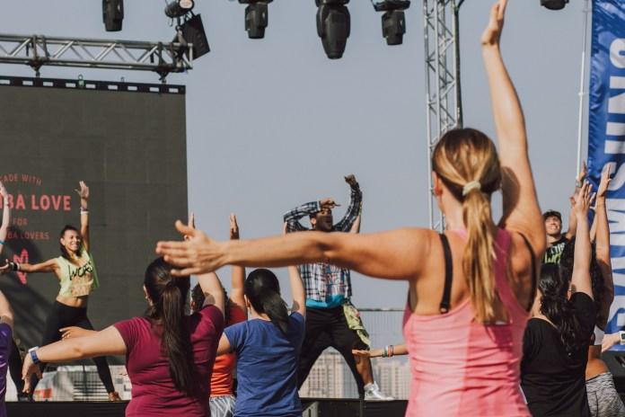 Woman in Pink Tank Top Raising Her Hands