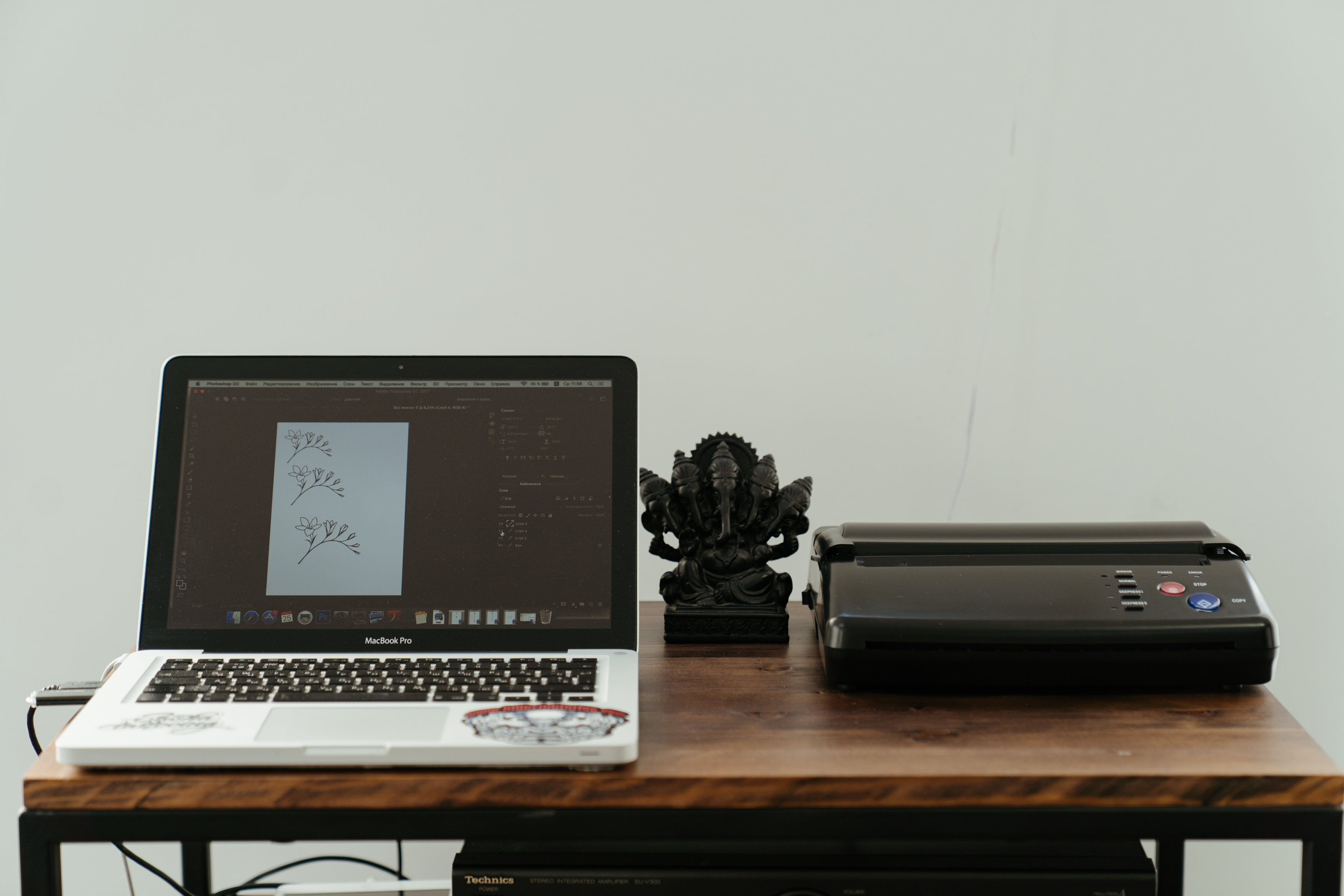 Macbook Pro connected to a printer. It has an image of flowers on the screen that is about to be printed.