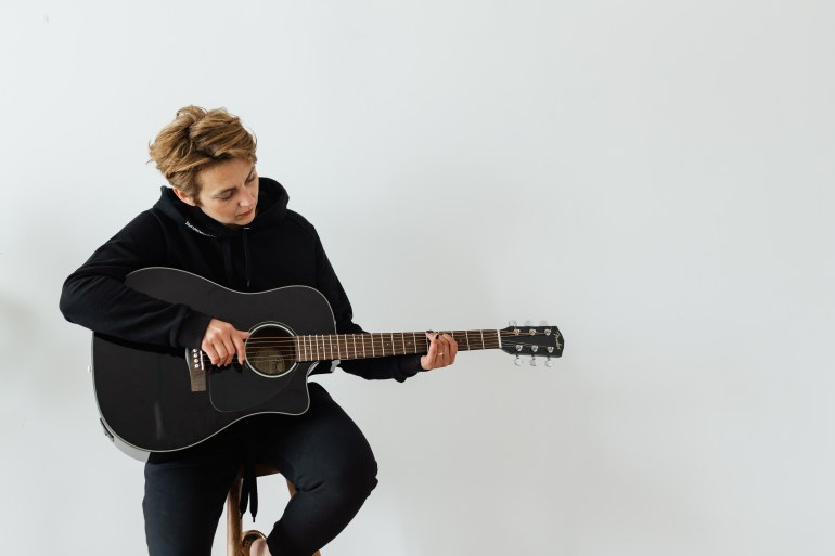 Man in Black Long Sleeve Shirt Playing Acoustic Guitar