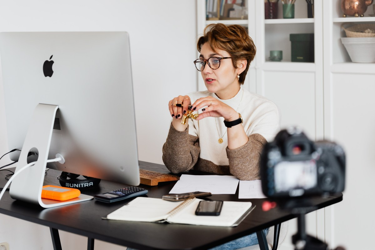A woman sits in front of a computer at her desk. She has papers, a pen, and a calculator. A camera faces her because she is teaching an online lesson.
