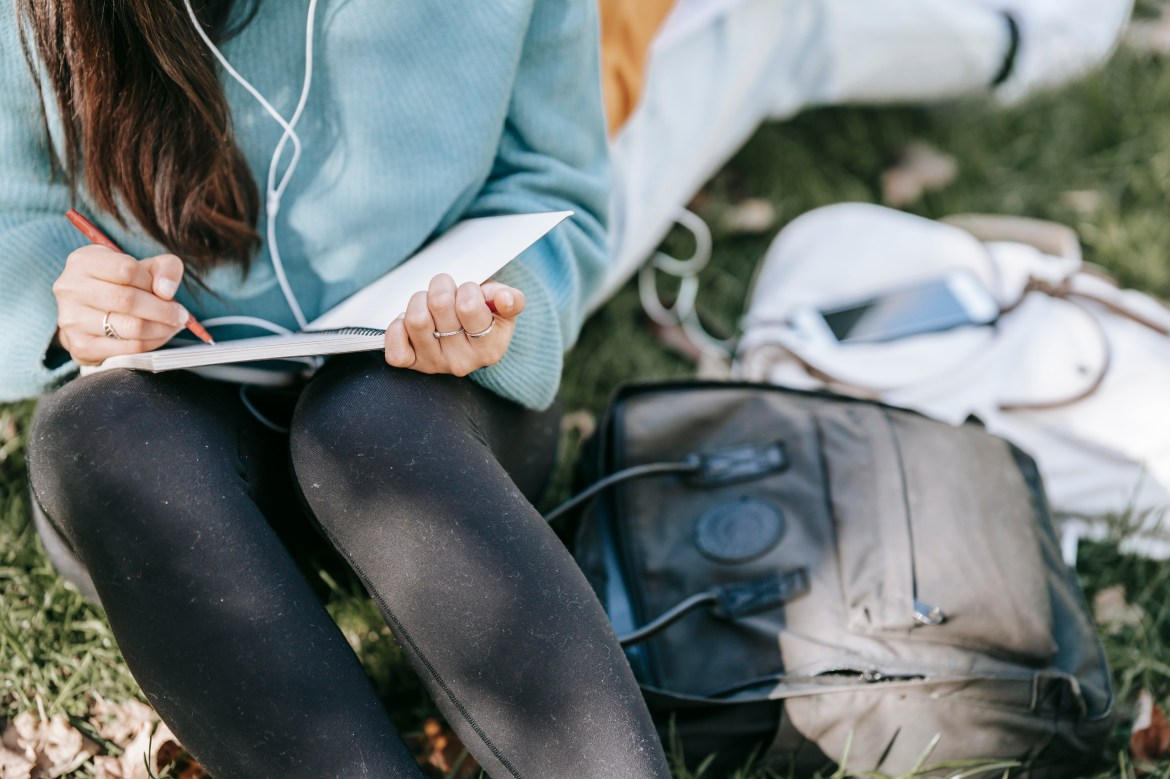 Crop anonymous female listening to music in earphones while writing in notebook near bags on grass