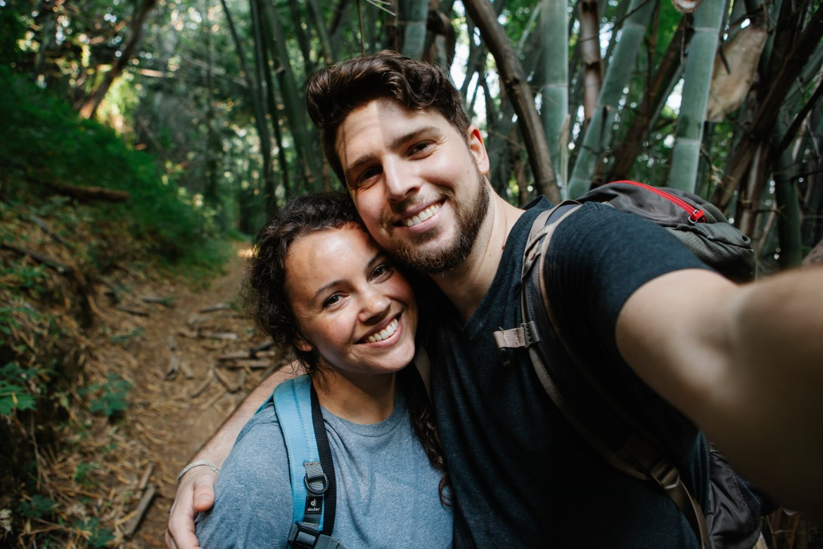Happy couple of travelers taking selfie in forest