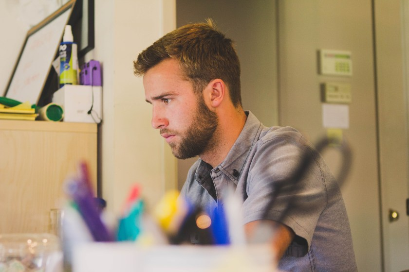 Selective Focus Photography of Man Sitting Near Desk