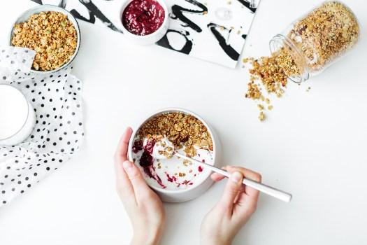 Persona que mezcla cereales, leche y mermelada de fresa en un recipiente de cerámica blanco