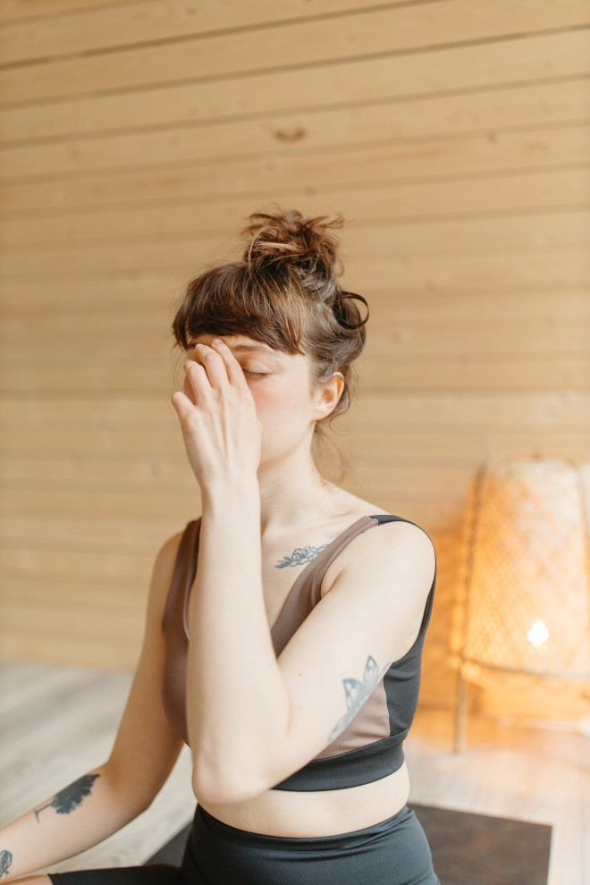 Woman in White Tank Top Covering Her Face With Her Hands