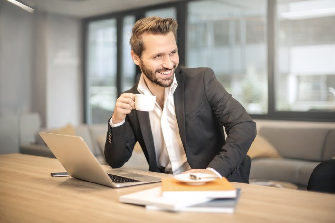 Man Holding White Teacup in Front of Gray Laptop