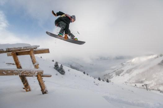 Hombre en negro Snowboard con enlace realiza un salto