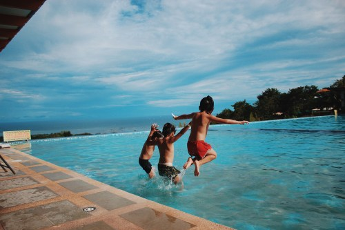 Three Boy's Jumping Into a swimming pool