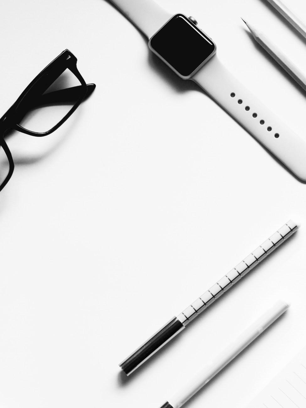 closed apple watch beside eyeglasses on table