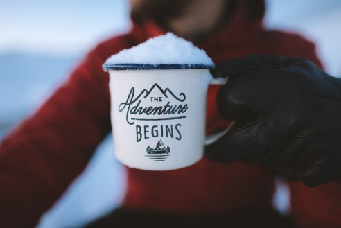 Selective Focus Photography of Person Holding the Adventure Begins Mug
