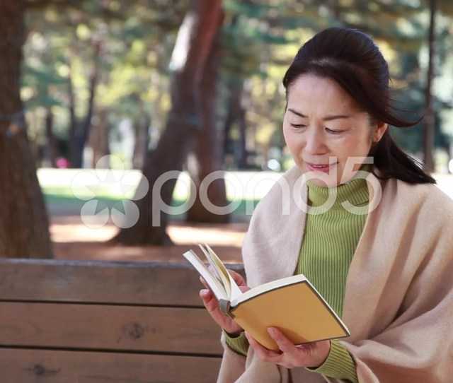 Japanese Mature Female Reading A Book On A Bench In A City Park In Autumn Clip 51137772