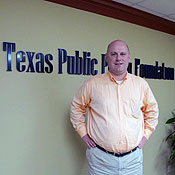 David Guenthner stands in front of a Texas Public Policy Foundation sign.