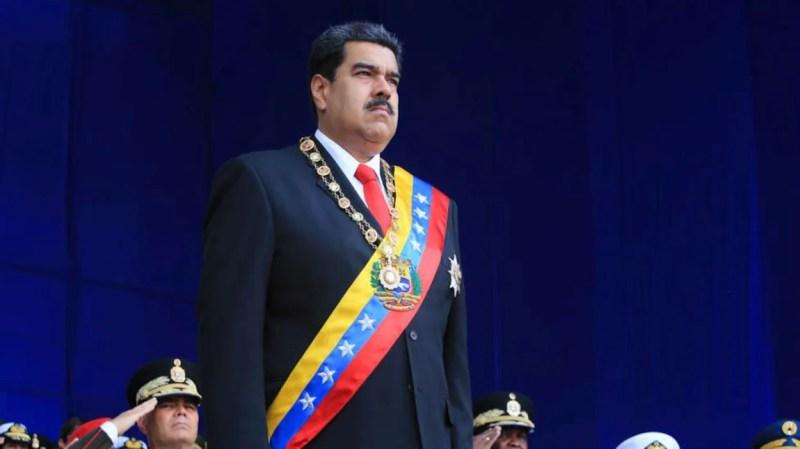 Le président Nicolas Maduro, l'air solennel, se tient sur la scène lors d'un grand événement militaire, à Caracas.