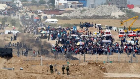 Des centaines de Palestiniens manifestent près d'une clôture protégée par trois soldats israéliens.