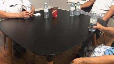 Gros plan sur une table avec des travailleurs assis autour d'une table. On ne voit pas leur visage afin de protéger leur identité.