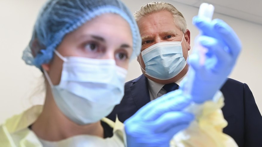 Doug Ford watches as a nurse prepares to administer a COVID-19 vaccine in Toronto.