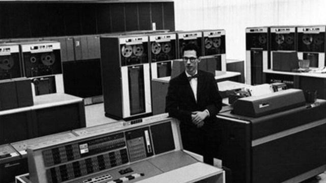 Fernando Corbató accoudé sur un poste informatique devant un énorme ordinateur.
