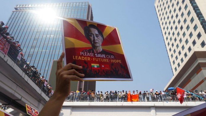 A hand holds up a poster of Aung San Suu Kyi.  It reads: