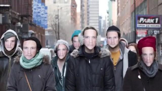 Un groupe de personnes marche dans la rue en portant tous le même masque.
