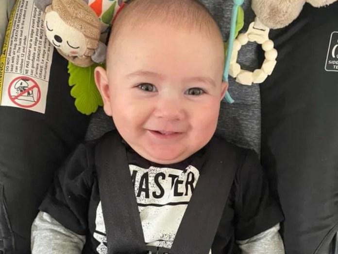 La photo d'un enfant de 8 mois dans son siège d'auto, souriant