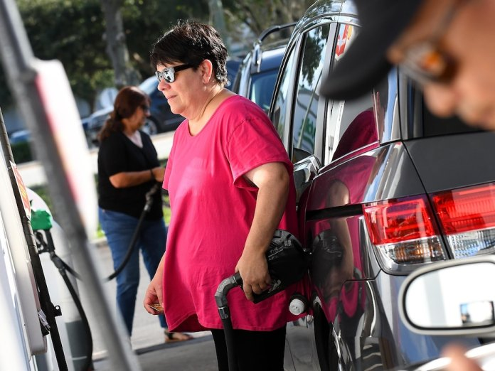 A woman puts gas in her car.