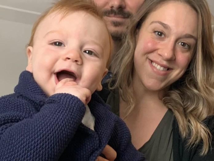 Jessica Dumont tient son fils dans ses bras, tout souriant. Le conjoint est en arrière plan.