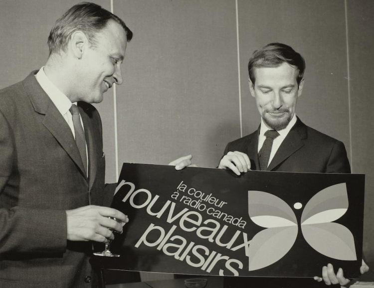 Raymond David, directeur général adjoint de la radiodiffusion française, en compagnie du graphiste Hubert Tison, tenant une affiche montrant le nouveau logo de la Société Radio-Canada, un papillon, symbole de la télévision en couleur.