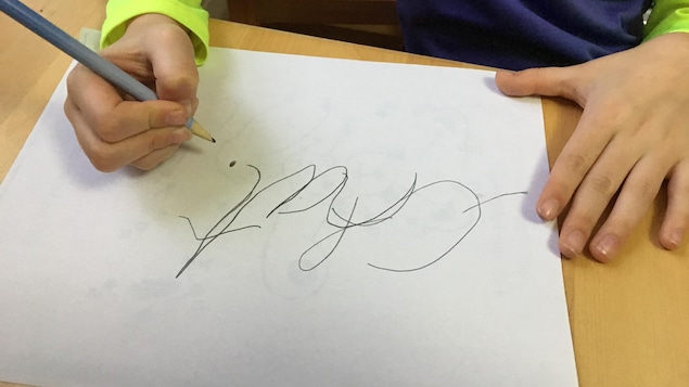 Photo d'une élève qui a écrit le mot «chat» en lettres attachées.