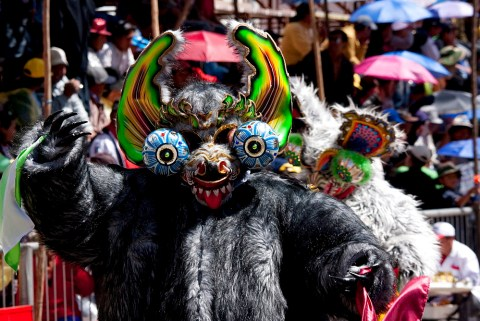 Diablada dancer wearing an elaborate devil mask and costume in the procession of the Carnaval de Oruro, Bolivia