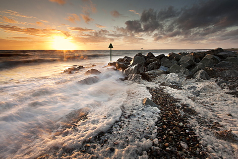 Gale driven surf and foam pile onto a shingle beach at sunset at Dinas Dinlle, Llyn Peninsula, Gwynedd, Wales, United Kingdom