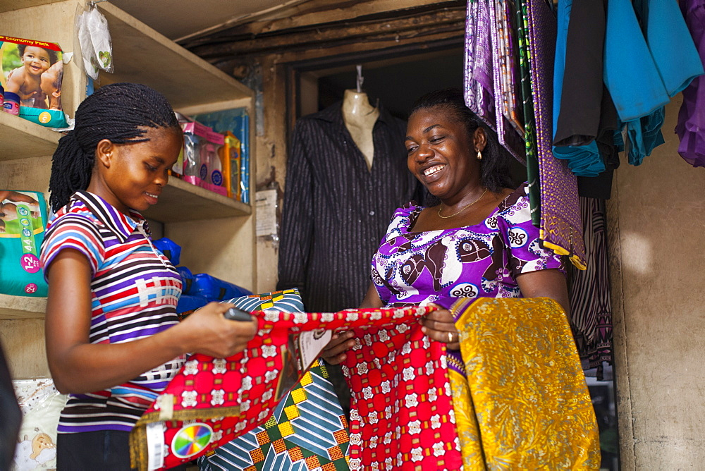 Stock photo of female shopkeeper showing different colourful materials to a potential customer