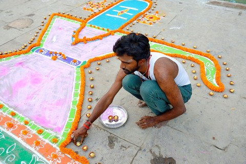 Diwali Stock Photo: India, Uttar Pradesh, Varanasi, Dev Deepawali festival, Hindu devotee setting earthen lamps.
