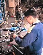 Un ragazzino al lavoro in un'officina meccanica a Napoli (foto Ansa)