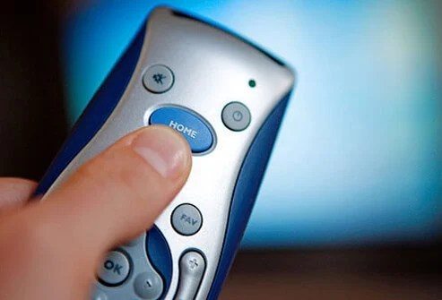 Photo of hand holding tv remote.