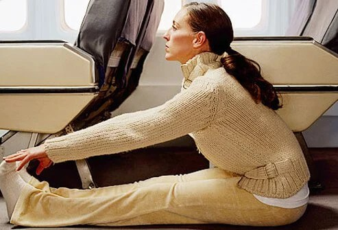 Photo of woman stretching legs in plane aisle.