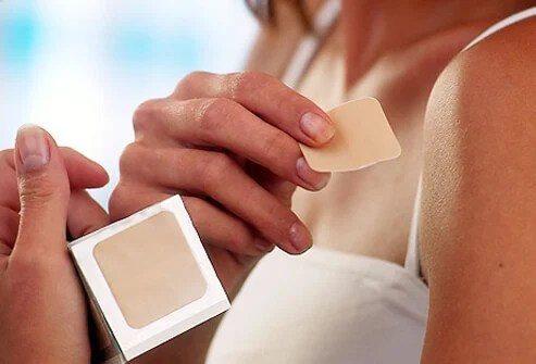 Woman applying nicotine patch to her shoulder.