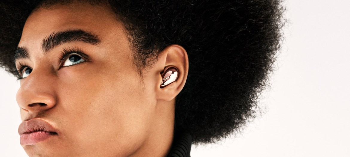 Partial view of a man with an afro wearing Galaxy Buds Live in Mystic Bronze. Screen zooms in for a close-up of his ear.