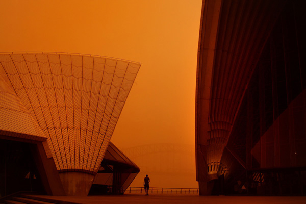 A man is dwarfed by the dust covered sails of the Sydney Opera House as tourists and locals head to the cities icons to take photographs of the blanket of dust covering the city of Sydney from a dust storm.