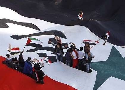 Pro-Syrian regime protesters appear from a huge Syrian flag as they wave Syrian and Baath party flags, during a protest against the Arab League decisions, in Damascus, Syria.