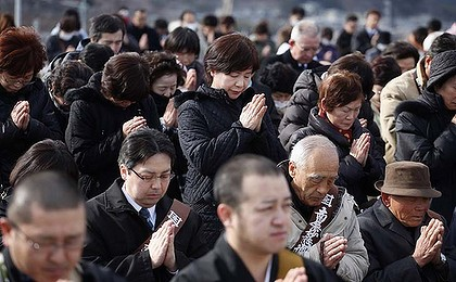 People take part in a moment of silence at 2.46pm during a ceremony in Ofunato.