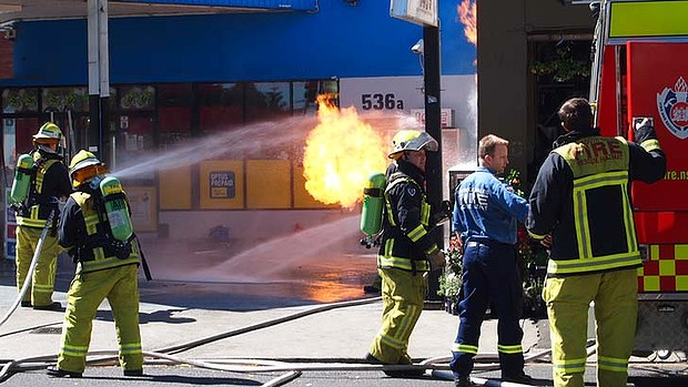 Flames shoot from gas bottles in a service station in King Street, Newtown, near the corner of Alice Street.