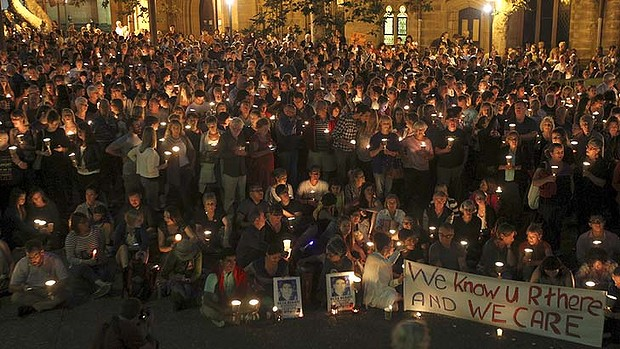 Crying out for change: Hundreds take part in the candle light vigil at Sydney's Town Hall.