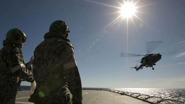A helicopter leaves the flight deck of HMAS Success as it searches for the missing plane.