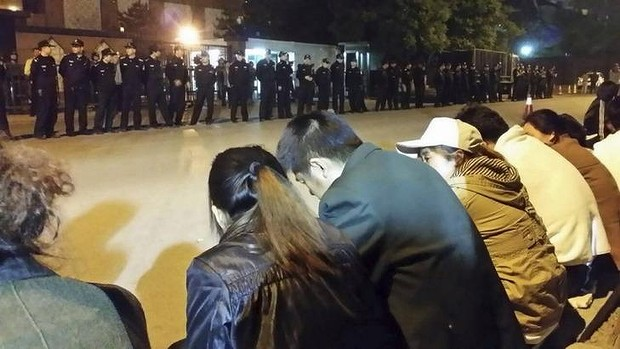 Family members of passengers aboard missing Malaysia Airlines Flight MH370 gather for a sit-in protest as security personnel stand guard outside the Malaysian embassy in Beijing.