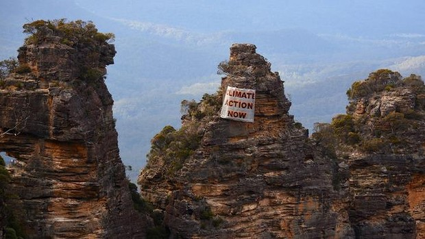 Human intervention: a banner hangs off the Three Sisters on Sunday.