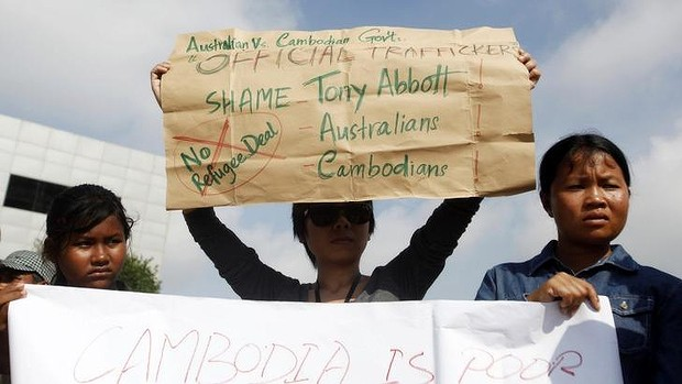 Protesters in Phnom Penh hold signs during a demonstration against Cambodia's plans to resettle intercepted refugees.