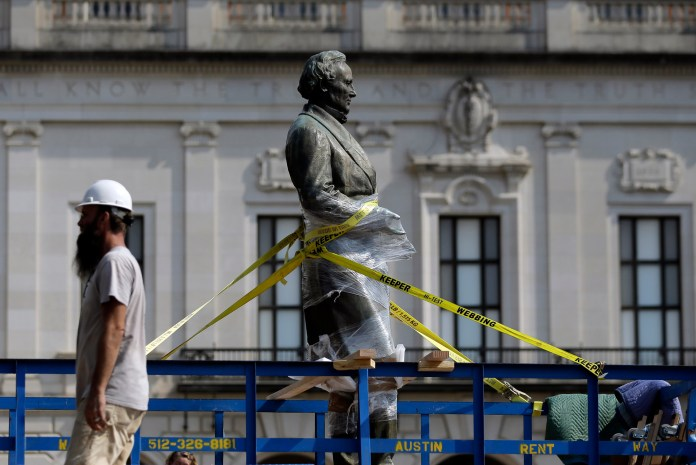 A statue of Confederate President Jefferson Davis is moved from its location in front of the school's main tower the University of Texas campus, Sunday, Aug. 30, 2015, in Austin, Texas. The Davis statue, which has been targeted by vandals and had come under increasing criticism, will be moved and placed in the school's Dolph Briscoe Center for American History as part of an educational display. (Eric Gay/AP)