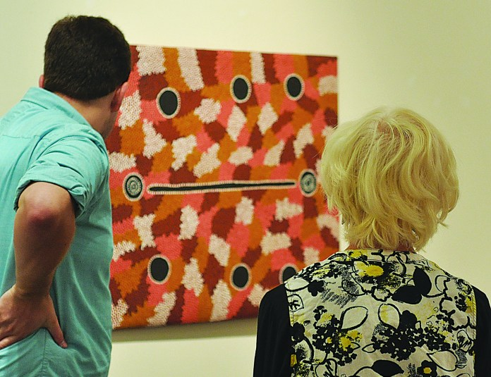 """Benton Museum vistors look at a piece of art included in the """"Dotted Dialogues"""" exhibit, which opened on Sept. 1. The exhibit demonstrates the importance of land, spirituality and history to the Aboriginal peoples of Australia through acrylic paintings on wood and on canvas. (Santiago Pelaez/The Daily Campus)"""