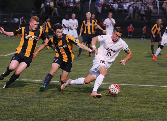 UConn junior defender Jakob Nerwinski dribbles away from two defenders during the Huskies' game against Quinnipiac at Joseph J. Morrone Stadium on Aug. 31, 2015. (Amar Batra/The Daily Campus)