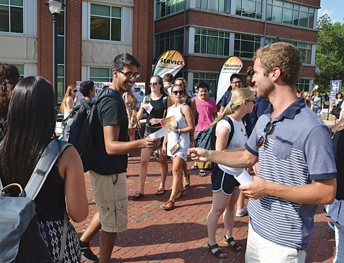 A student receives an informational handout during the fall Involvement Fair on Fairfield Way on Wednesday, Sept. 9, 2015. (Amar Batra/The Daily Campus)